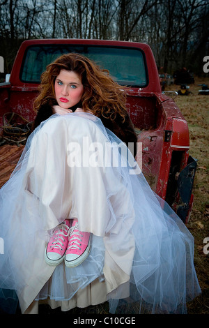 A teenage girl sits on an old rusted truck wearing a white prom dress and pink sneakers. - Stock Photo