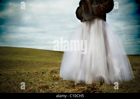 A teenage girl stands in a Virginia field wearing white prom dress and mink coat. - Stock Photo