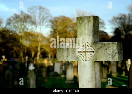 A close up of a Celtic cross shaped gravestone in a Sunderland cemetery with out of focus trees and graves in the - Stock Photo