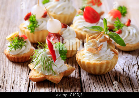 Variety of pastry-based canapes with various toppings - Stock Photo