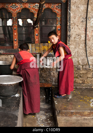 Two young Bhutanese Buddhist monks clean the dishes of the monastery after a meal at a temple in Central Bhutan - Stock Photo