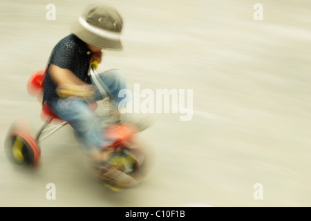 Boy on tricycle - Stock Photo