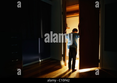 Boy stands at cupboard doors lit from within - Stock Photo