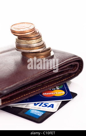 Empty pursue with a pile of coins and credit cards - Stock Photo