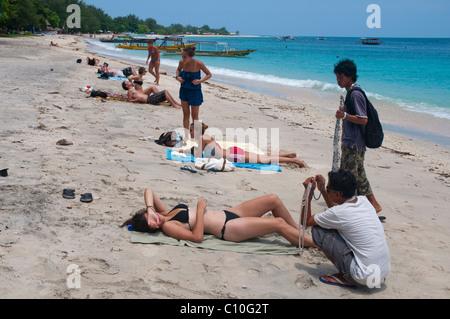 Trinket sellers pestering sunbather on beach on Gili Trawangan a small island off the costs of Lombok - Stock Photo