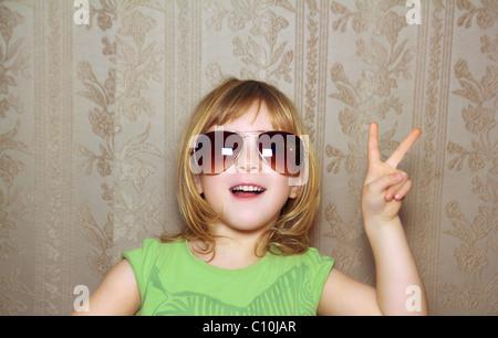 hand victory gesture little girl funny sunglasses retro wallpaper - Stock Photo