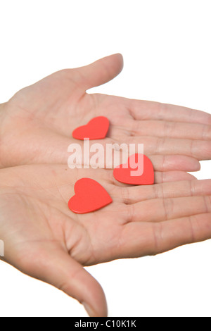 Three red wooden hearts in two outstretched hands - Stock Photo