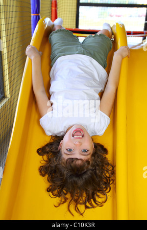 upside down little girl on playground slide laughing happy play - Stock Photo