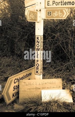 Sign post in South Devon with 'Daffodils and Vegetables' for sale sign - Stock Photo