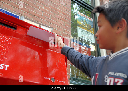 Young boy posting letter - Stock Photo