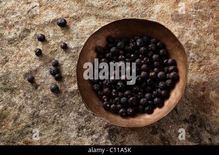 Juniper berries (Juniperus) in a copper bowl on a stone surface - Stock Photo