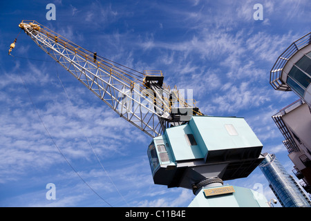 A now defunct Stothert and Pitt dockside crane stands in juxtaposition to the 'Lipstick', Gunwharf Quays, Portsmouth. - Stock Photo
