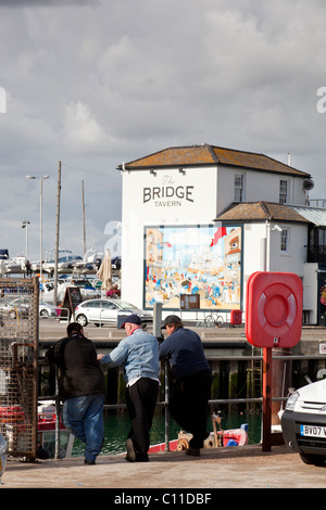 Fishermen chat on the dockside in Camber Dock with the historic Bridge Tavern in the background. - Stock Photo