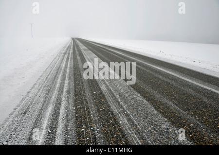Snowy and slippery road in fog, winter shot, Swabian Alb, Germany, Europe - Stock Photo