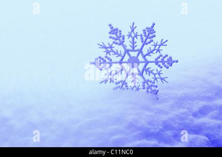 Decorative snowflake in snow - Stock Photo
