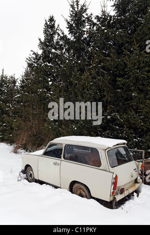 Discarded Trabant 600 S, parked in the snow under fir trees, Harz, Saxony-Anhalt, Germany, Europe - Stock Photo