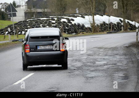 Car avoiding potholes, road damage on the L286, North Rhine-Westphalia, Germany, Europe - Stock Photo