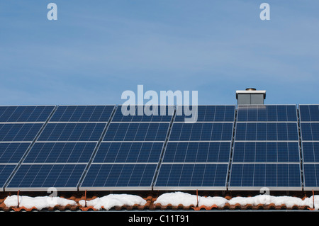 Solar panels on the roof of a house with patches of snow, renewable energy - Stock Photo
