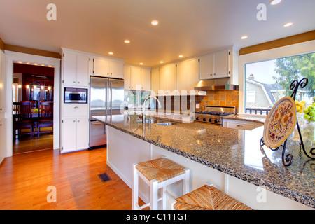 Luxury white kitchen, oak floors and beautiful granite - Stock Photo