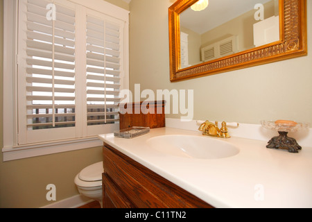 Classic beige bathroom with white and wood cabinets, tiles and beige walls. Tacoma, WA - Stock Photo