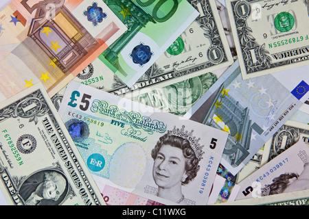 A mixture of U.S. dollar bills, euros and British pound notes - Stock Photo