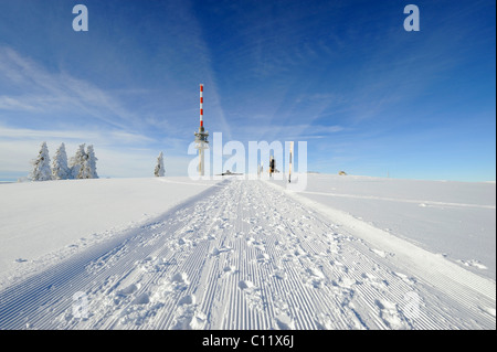 Rolled snow trail on the 1493m high Mt. Feldberg in the Black Forest, on the horizon the new Feldbergturm antenna - Stock Photo