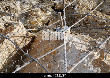 Wire mesh securing a slope from rockfall or landslide, Costa Blanca, Alicante province, Spain, Europe - Stock Photo