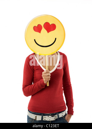 young adult woman holding emoticon with red hearts on white background. Vertical shape, front view, waist up - Stock Photo
