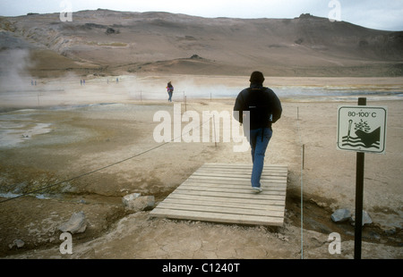 A tourist on a boardwalk passes a sign warning of very hot ground at the Namaskard solfatara field in northern Iceland - Stock Photo