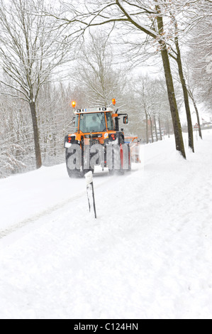 Trecker clearing snow off a country road - Stock Photo