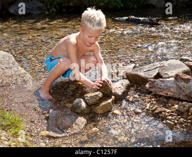 Boy, six years old, playing in a stream - Stock Photo