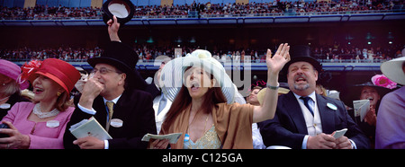 Race goers celebrate a race finish during the race meeting at Royal Ascot Race Course. - Stock Photo