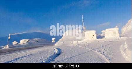 US - Canadian Border, icy road, snow covered highway maintenance buildings, White Pass, Coastal Range, South Klondike - Stock Photo