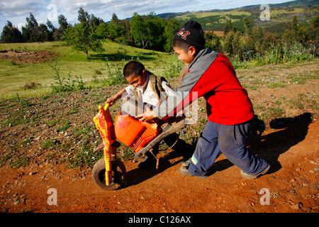 Two boys pushing a broken tricycle, Mapuche Indians, near Concepción, Southern Chile, Chile, South America - Stock Photo