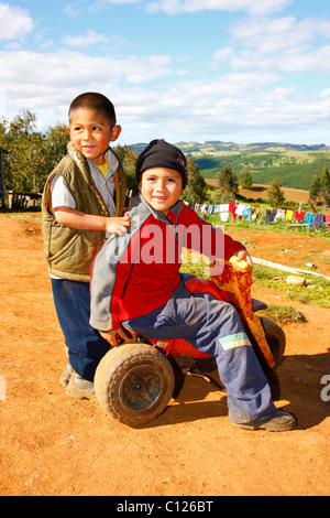 Two boys with a tricycle, Mapuche Indians, near Concepción, Southern Chile, Chile, South America - Stock Photo