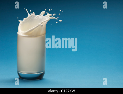 Splash of milk from the glass on a blue background - Stock Photo