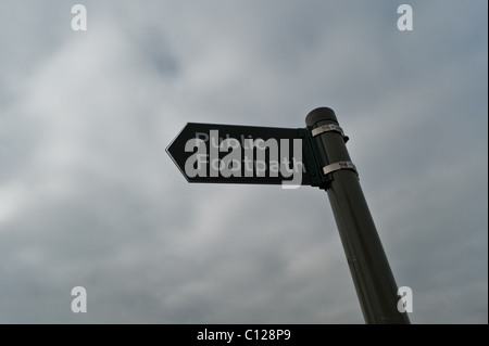 A public footpath signpost in the United Kingdom with a dark sky backdrop. - Stock Photo