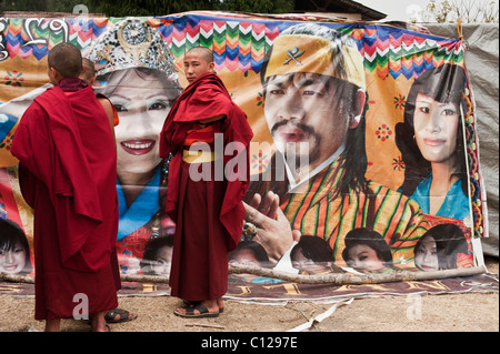 Buddhist monks ponder the virtues of buying a ticket to a new film being shown in a tent at a festival in rural - Stock Photo