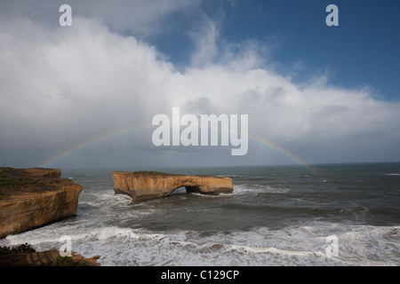 London arch, formerly London bridge before the collapse, surrounded by rainbow. Great Ocean Road, Victoria, Australia - Stock Photo