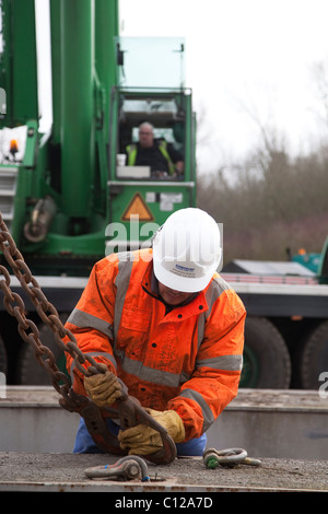 Crane driver assisting with unloading of heavy equipment during the Delivery of Alstom National Grid Transformer, - Stock Photo
