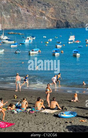 La Gomera, Canary Islands. Family sunbathers on the holiday beach of Puerto de Vueltas, Valle Gran Rey - Stock Photo