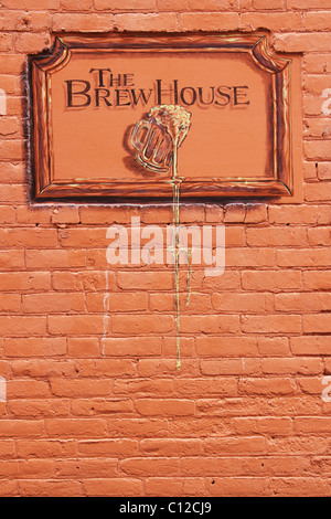 Sign for The Brew House. A bar in North Manchester, Indiana, USA. Near three dimensional painting on a brick wall. - Stock Photo