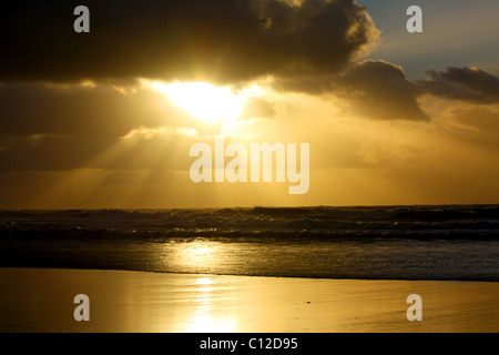 40,151.06066a Sun rays sunbeams dark clouds cloud layers golden glow shining sunlight onto ocean waves beach. - Stock Photo
