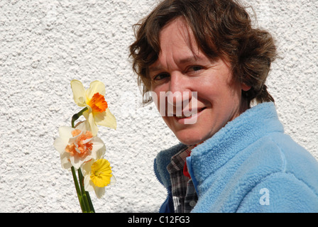 woman with bunch of daffodils, portrait outdoors - Stock Photo
