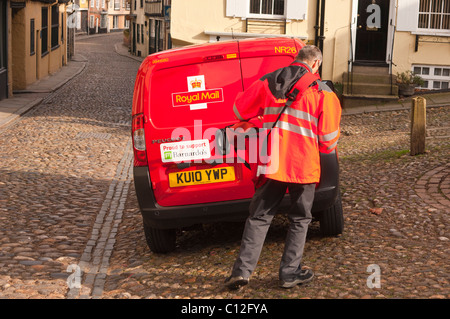A Royal Mail postman delivering mail in Elm hill in Norwich , Norfolk , England , Britain , Uk - Stock Photo