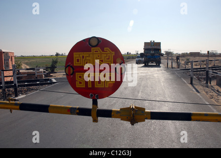 Lorry, truck at level-crossing with STOP sign in Rajasthan, India - Stock Photo