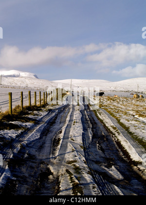 Looking up a snowy road towards a Hill farm in the Scottish Highlands in winter. - Stock Photo