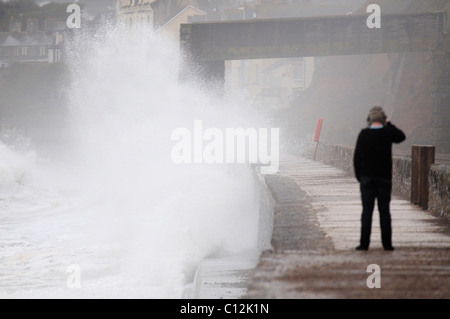 Young man taking photos of the sea splashing up against the sea wall at Dawlish in Devon - Stock Photo