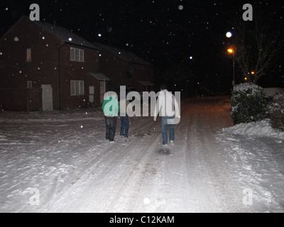 young men walking down the road in the snow at night