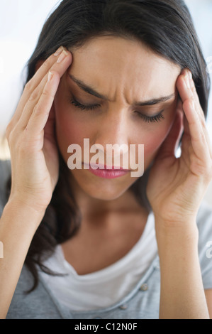 Woman suffering from headache holding head in hands - Stock Photo